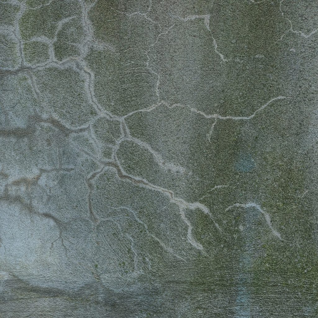 greenish concrete slab with minor cracks and patches